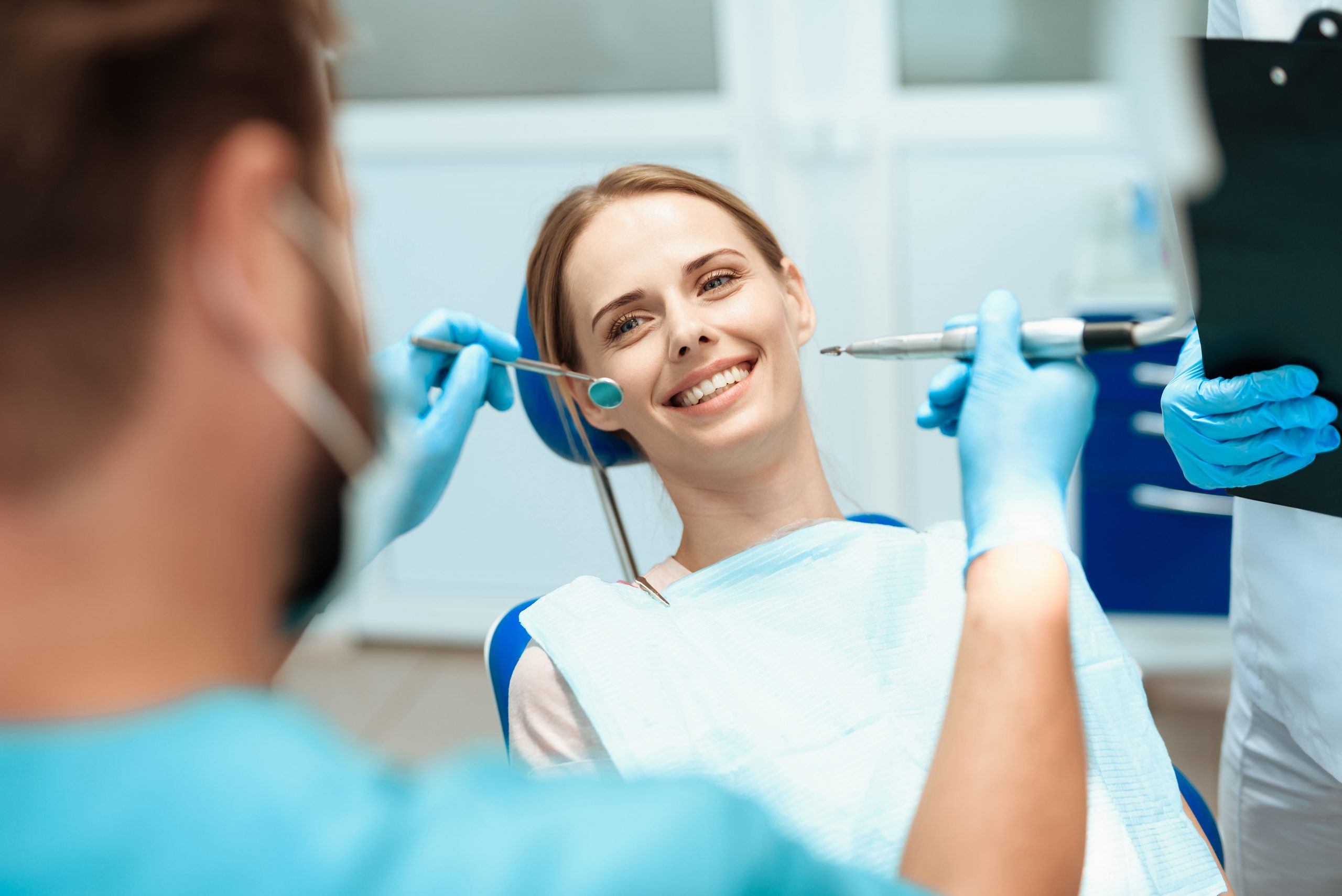 Best Dentist in Newton | Woman smiling on dental chair.